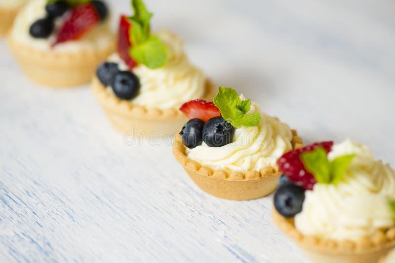 Tartlets med gräddost och jordgubbar arkivfoton