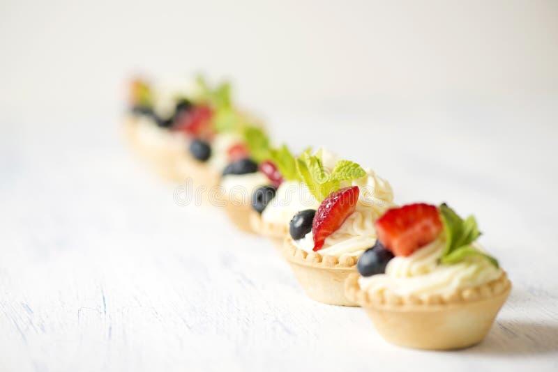 Tartlets med gräddost och jordgubbar royaltyfria foton