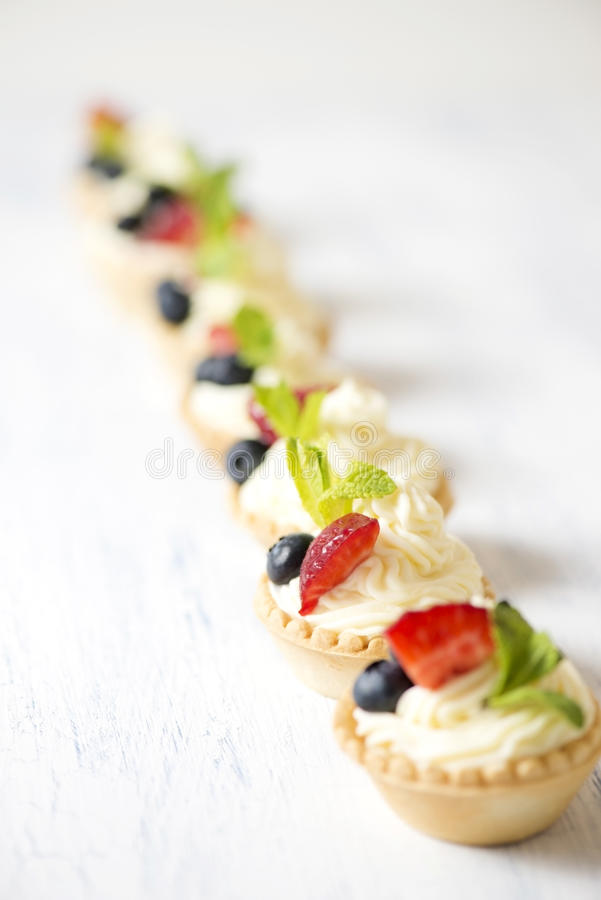Tartlets med gräddost och jordgubbar arkivfoto