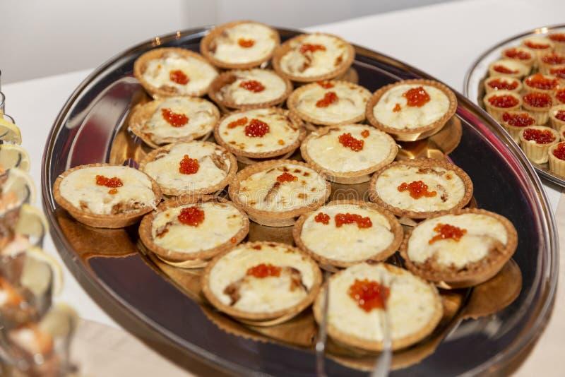 Tartlets met rode kaviaar op een schaal op de buffettafel Festive lijst die bij gebeurtenissen plaatst Sluiten royalty-vrije stock fotografie