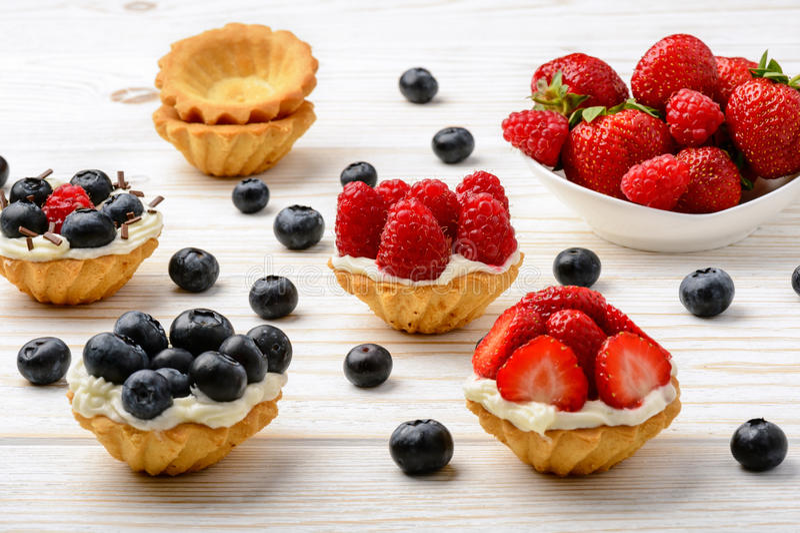 Tartlets met room, bosbessen, frambozen en aardbeien op witte houten lijst Selectieve nadruk stock foto's