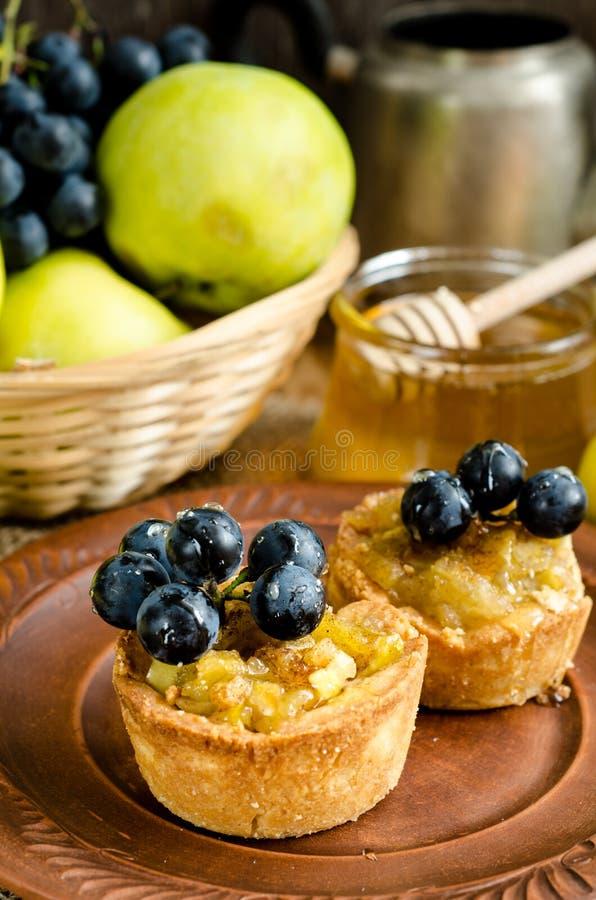 Tartlets mit Apfel, Trauben und Honig lizenzfreies stockbild