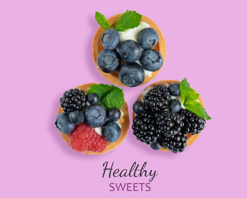 Tartlets mit Weichkäse und Beeren der Himbeere, Brombeere, Blaubeere auf einem rosa hölzernen Hintergrund K?stlich und gesund stockbilder