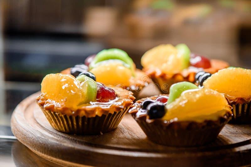 Tartlets o torta deliciosos de la baya con con la naranja, el kiwi, y las bayas en un primer del tablero de madera foto de archivo libre de regalías