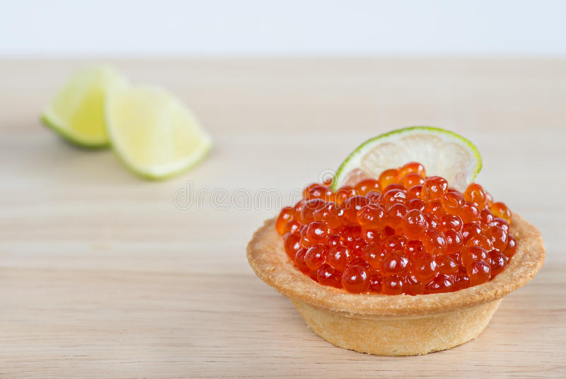 Tartlets with red caviar and lime. On light wooden background, selective focus stock photography