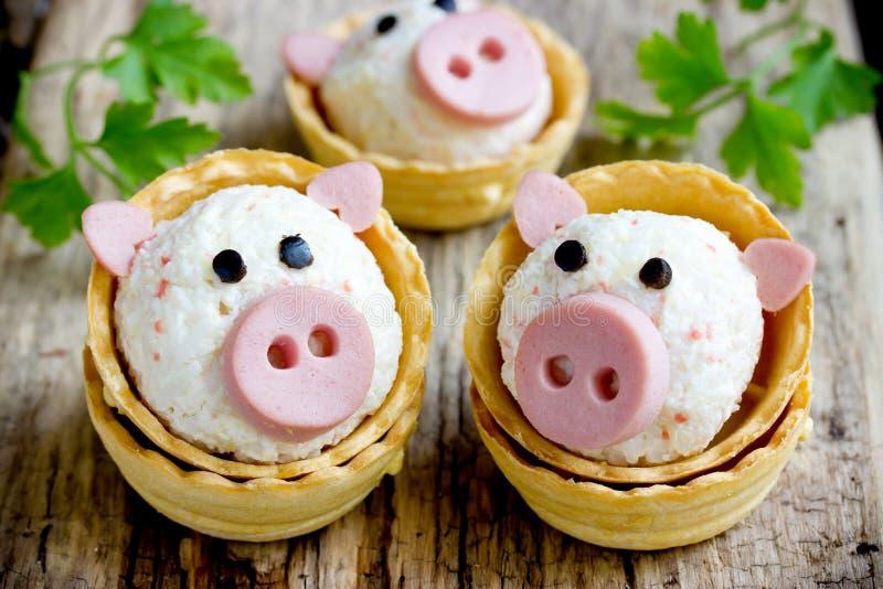 Tartlets rellenos con arroz, palillos del cangrejo, huevo, forma del bocado del ajo de cerdos divertidos imagen de archivo libre de regalías
