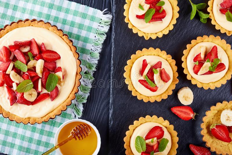 Tartlets and tart with strawberries, banana, mint stock photo