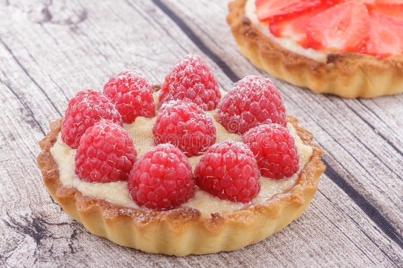 Tartlets. A Tartlet with Fresh Raspberries on a Rustic Table stock photo