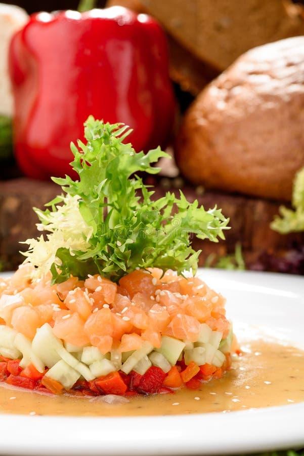 Tartre saumoné délicieux avec de la salade d'un plat blanc sur un beau fond en bois foncé Déjeuner sain des saumons crus photographie stock
