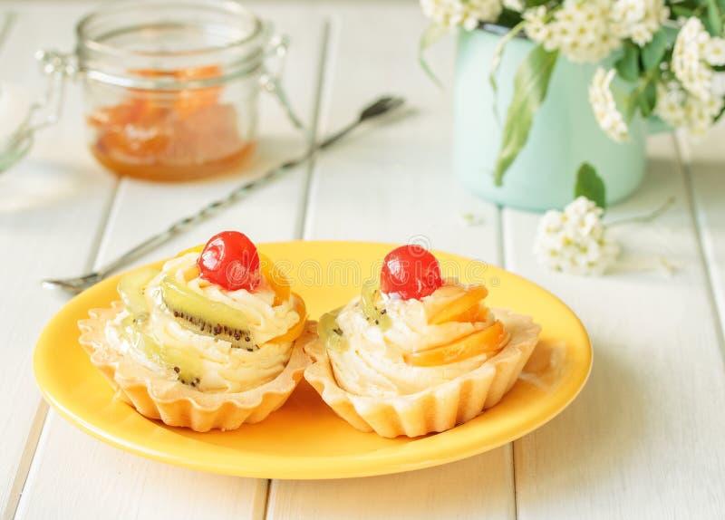 Tarts με την κρέμα φρούτων και βανίλιας με το κεράσι και το ακτινίδιο στοκ φωτογραφίες