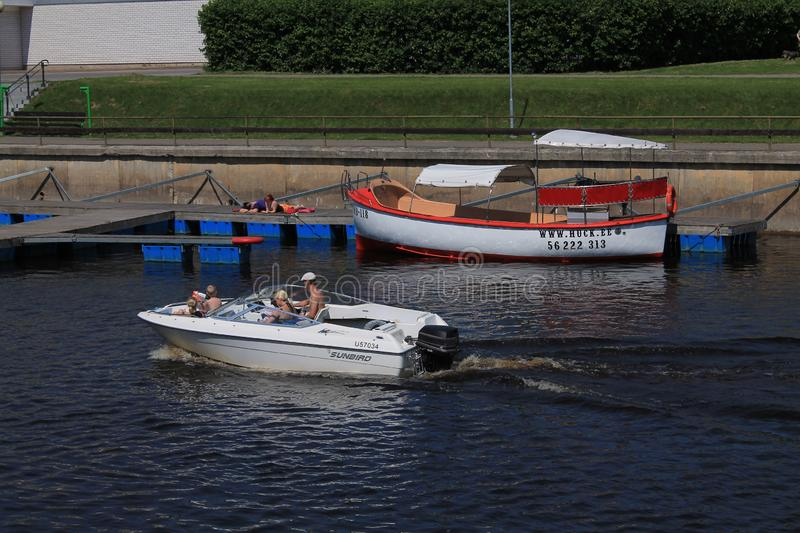 A family with three children makes a boat trip on a motor boat. Two girls sunbathe on the pier. Tartu, Estonia / July 08, 2019: A family with three children royalty free stock photo
