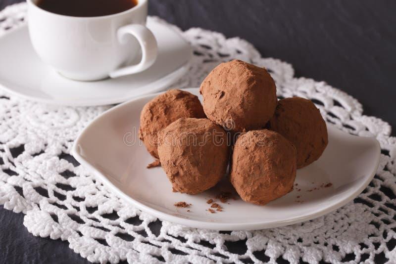 Tartufi di cioccolato su un primo piano del caffè e del piatto sulla tavola immagine stock
