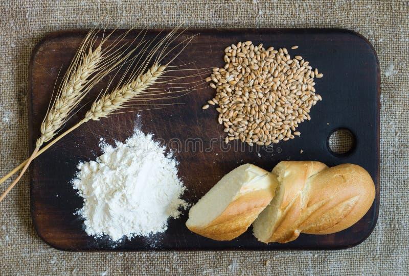 Tarweoren, korrels, bloem en gesneden brood op een keukenraad op een het ontslaan achtergrond stock afbeelding