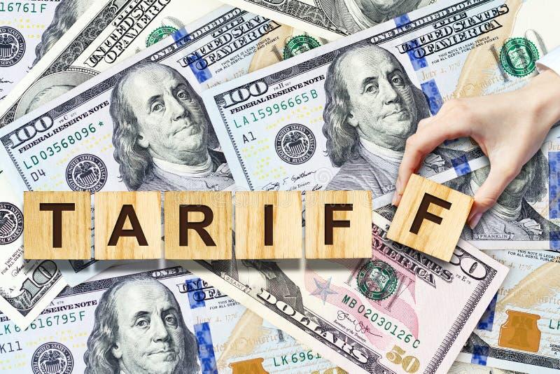 Taryfa, Żeński ręcznie robiony w górę inskrypcji na drewnianych blokach na tle Dolarowi banknoty Biznes, finanse zdjęcie royalty free