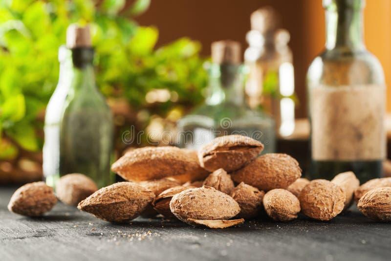 Tas d'amande dans la coquille sur des bouteilles d'une table en bois noire et en verre de cru avec la verdure à l'arrière-plan image stock