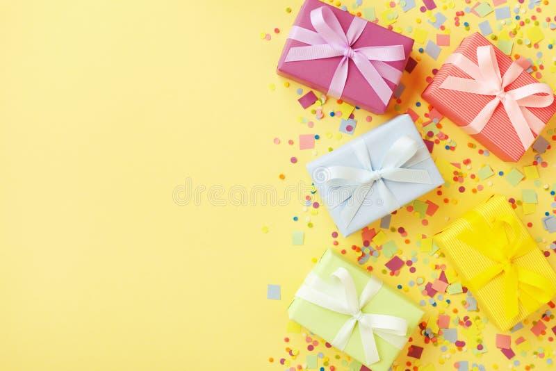Tas de cadeau ou de boîtes actuelles et confettis sur la vue supérieure en pastel de table Fond de joyeux anniversaire photos libres de droits