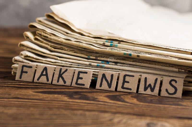 Tas de vieux journaux près des places de rectangle de carton avec de fausses nouvelles d'inscription manuscrite sur la vieille ta images libres de droits