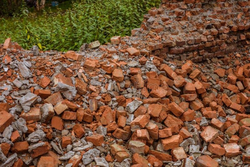 Tas des briques rouges qui sont restées à la maison après détruit photographie stock