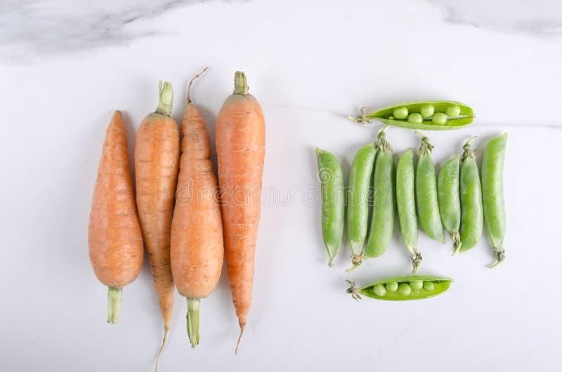 Tas des carottes et des pois doux dans des cosses sur la table de cuisine blanche photo stock