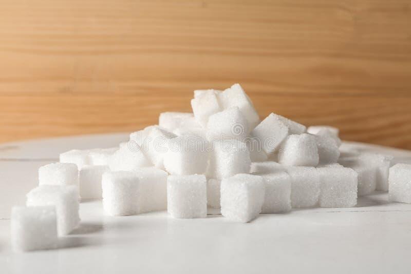 Tas des cubes en sucre raffiné sur la table images stock