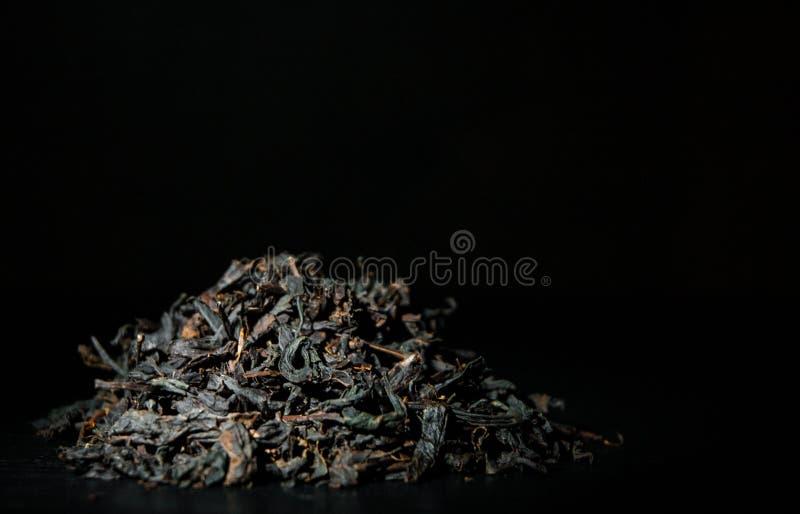Tas des feuilles de thé noires sur le vieux fond en bois foncé images stock