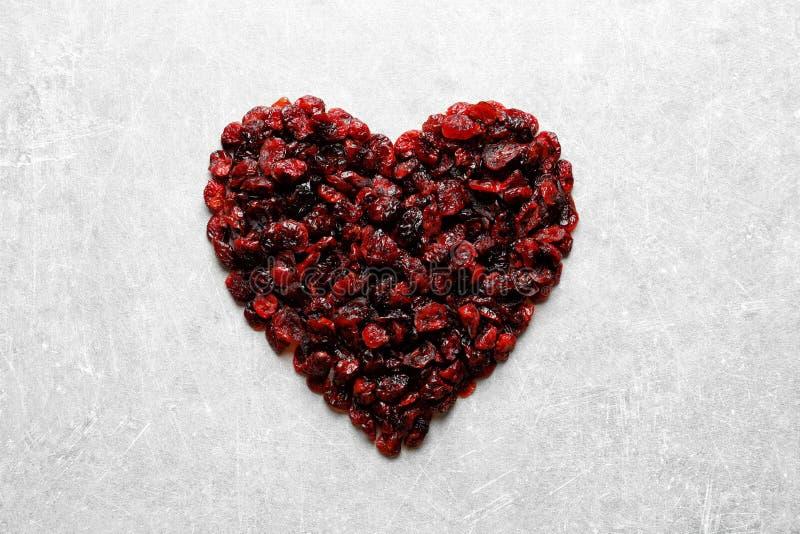 Tas en forme de coeur des canneberges douces sur le fond de couleur, vue supérieure Fruits secs photographie stock