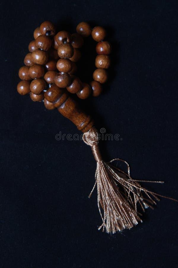 Tasbih de madeira, amor dá forma ao grânulo de oração dos povos do Islã no fundo preto imagem de stock royalty free