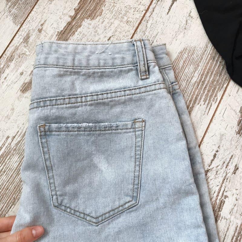 Tasca posteriore dei jeans su un fondo di legno fotografia stock