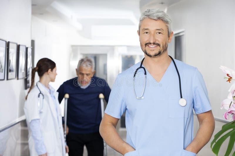 Tasche del dottore With Hands In che stanno con il collega ed il paziente fotografie stock