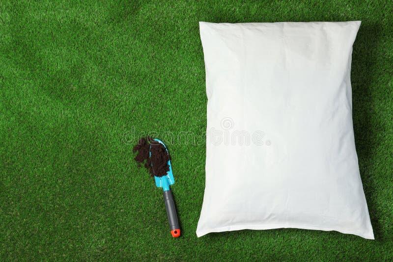 Tasche mit Boden und Schaufel auf grünem Gras, flache Lage gardening lizenzfreie stockfotos