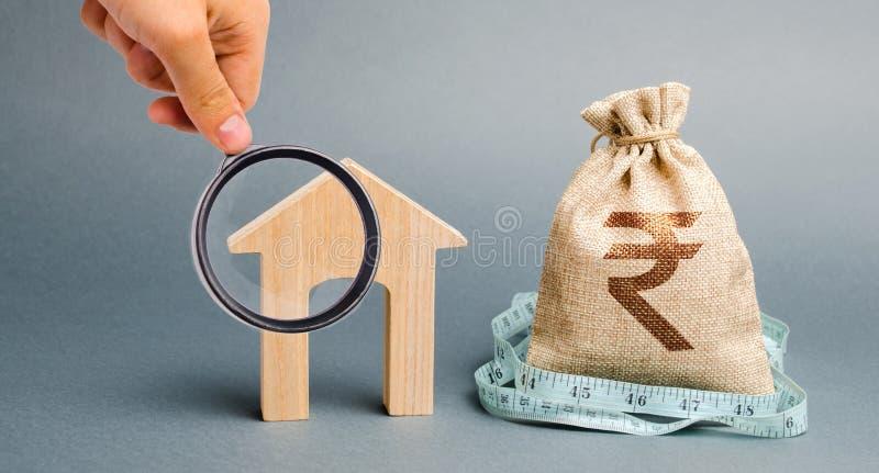 Tasche mit Geld und Ma?band mit Holzh?user Das Konzept eines begrenzten Immobilienbudgets Marktkrise Bankrott niedrig stockbilder