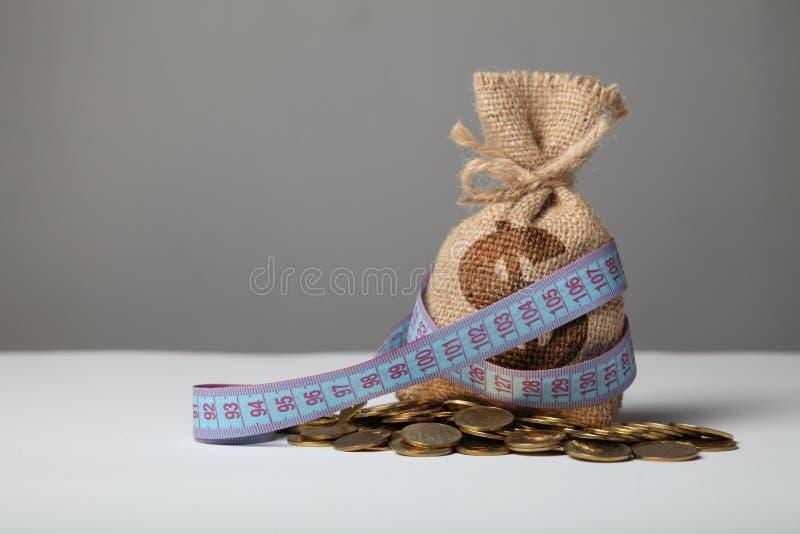 Tasche mit Geld und messendem Band auf Goldm?nzen Geldmangel, Armut und Einsparungen lizenzfreie stockfotos