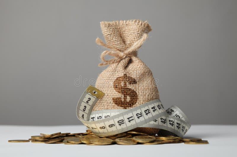 Tasche mit Geld und messendem Band auf Goldm?nzen Geldmangel, Armut und Einsparungen stockfotografie