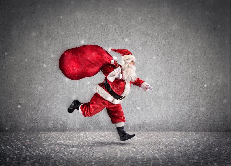 Tasche Santa Claus Running Withs A von Geschenken auf Weise lizenzfreies stockfoto