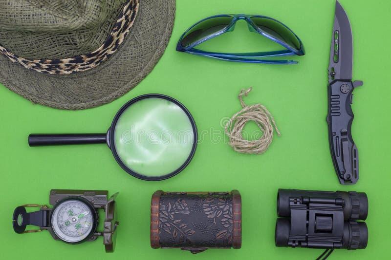 Taschenmesser mit Kompass, Papier, Bleistift, Notizbuch, Hut, Seil, Lupe auf Grünbuchhintergrund lizenzfreie stockbilder