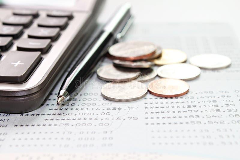 Taschenrechner, Münzen und Stift auf Sparkontosparbuch oder Finanzberichten lizenzfreies stockbild