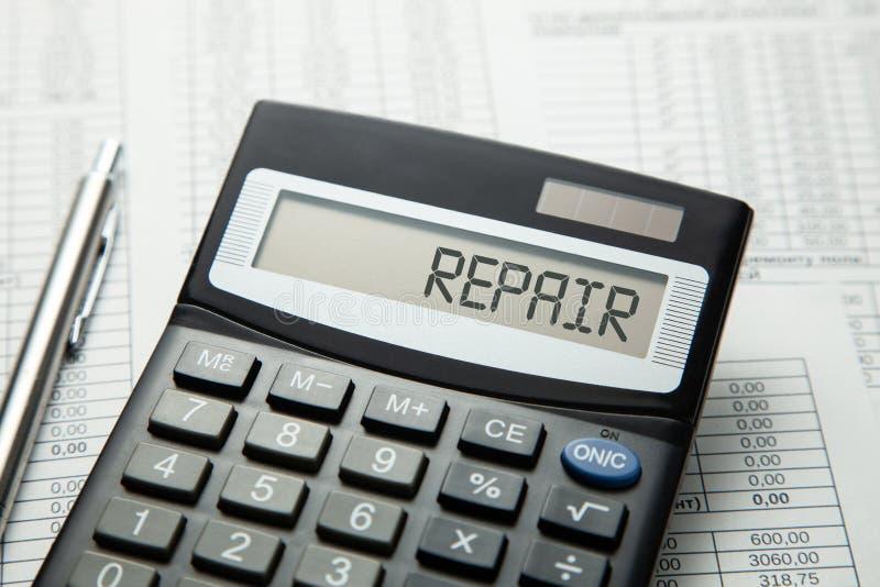 Taschenrechner mit der Aufschrift auf der REPARATUR-Anzeige auf den Papierauflagen Ausgangs- oder Autoreparatur lizenzfreie stockfotos