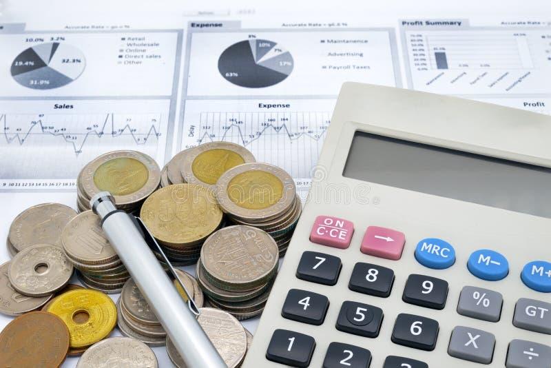 Taschenrechner, Stift und Stapel Münzen auf schriftlichem Diagramm stockbilder