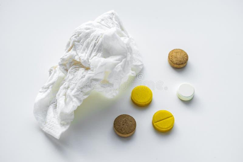 Taschentuch und Pillen auf der weißen Tabelle Das Konzept von Kälten stockfotografie