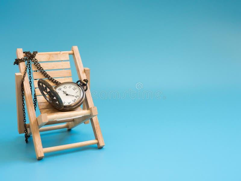 Taschenuhr auf dem hölzernen Strandstuhl auf dem blauen Hintergrund lokalisiert Kopieren Sie Raum für Text und Inhalt Konzept von lizenzfreies stockfoto