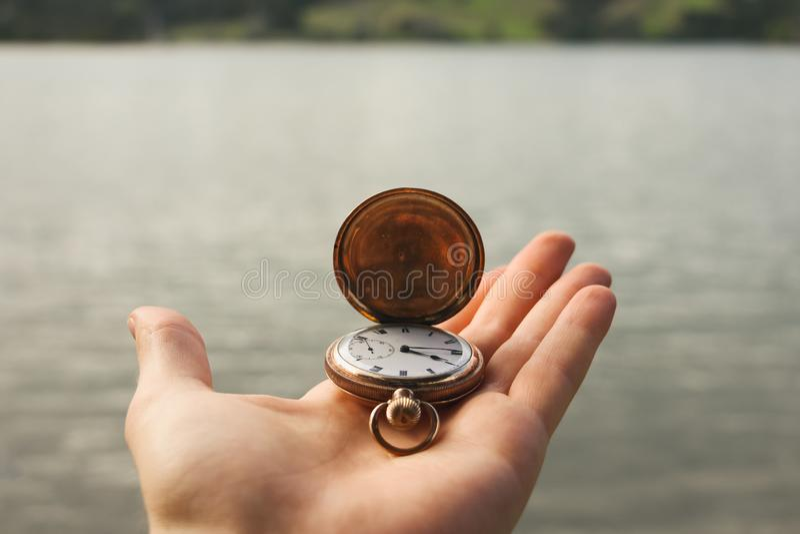 Taschenuhr in der Hand über Wasser stockfotos