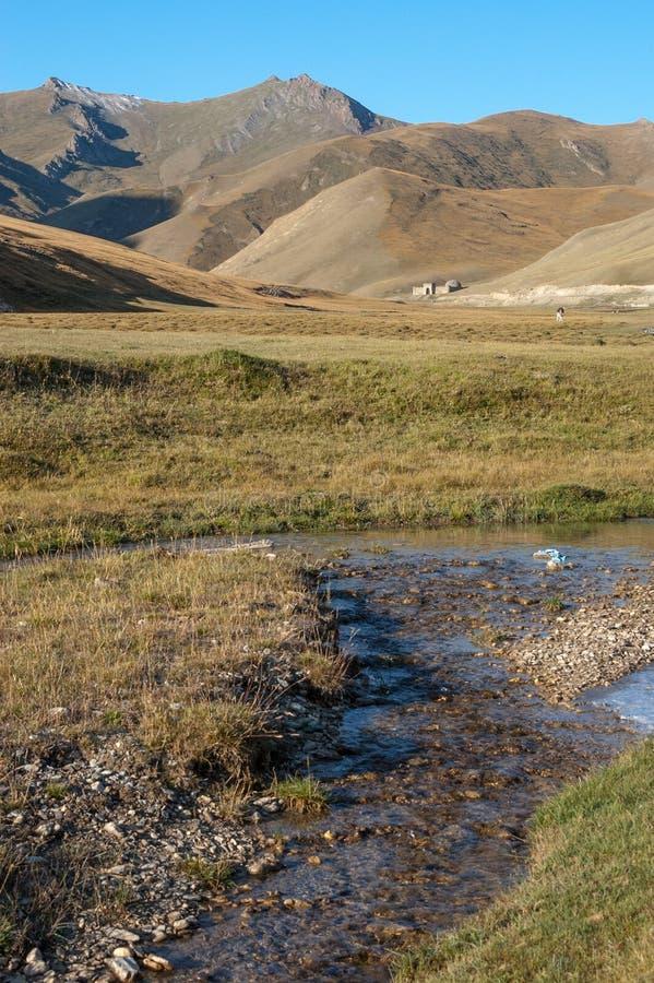 View along small creek to stone caravanserai of Tash Rabat stock photo