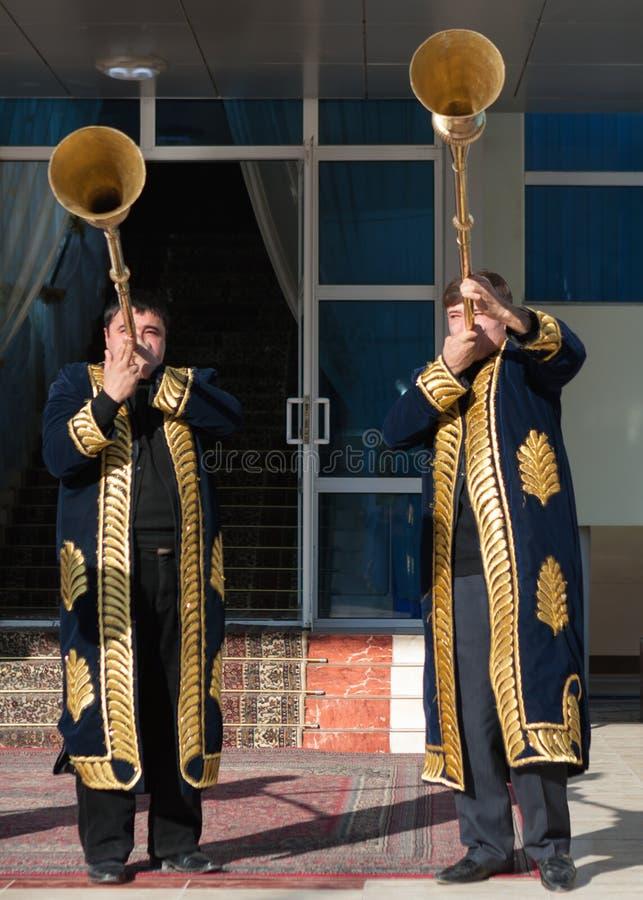 TASHKENT USBEQUISTÃO - 9 de dezembro de 2011: Homens do músico nos kaftans tradicionais que jogam o karnay fotografia de stock royalty free