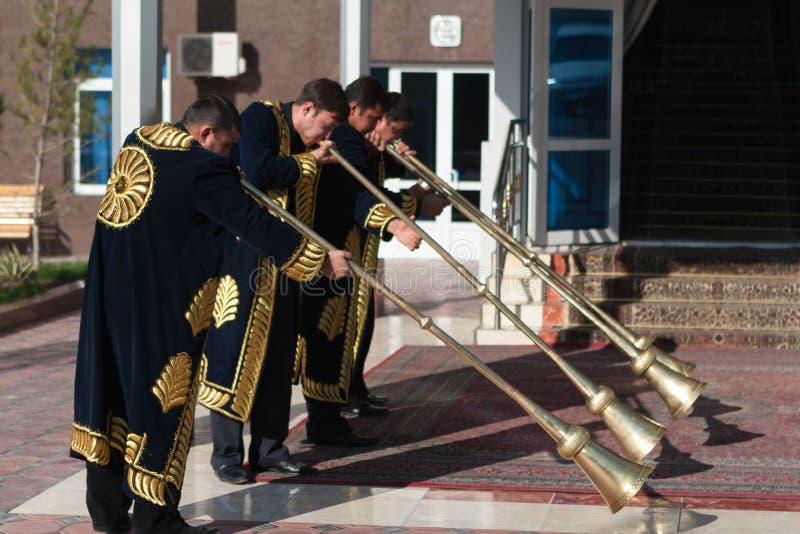 TASHKENT USBEQUISTÃO - 9 de dezembro de 2011: Homens do músico nos kaftans tradicionais que jogam o karnay fotos de stock royalty free