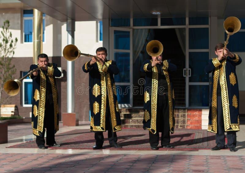 TASHKENT UZBEKISTÁN - 9 de diciembre de 2011: Hombres del músico en los kaftans tradicionales que juegan el karnay imagen de archivo libre de regalías
