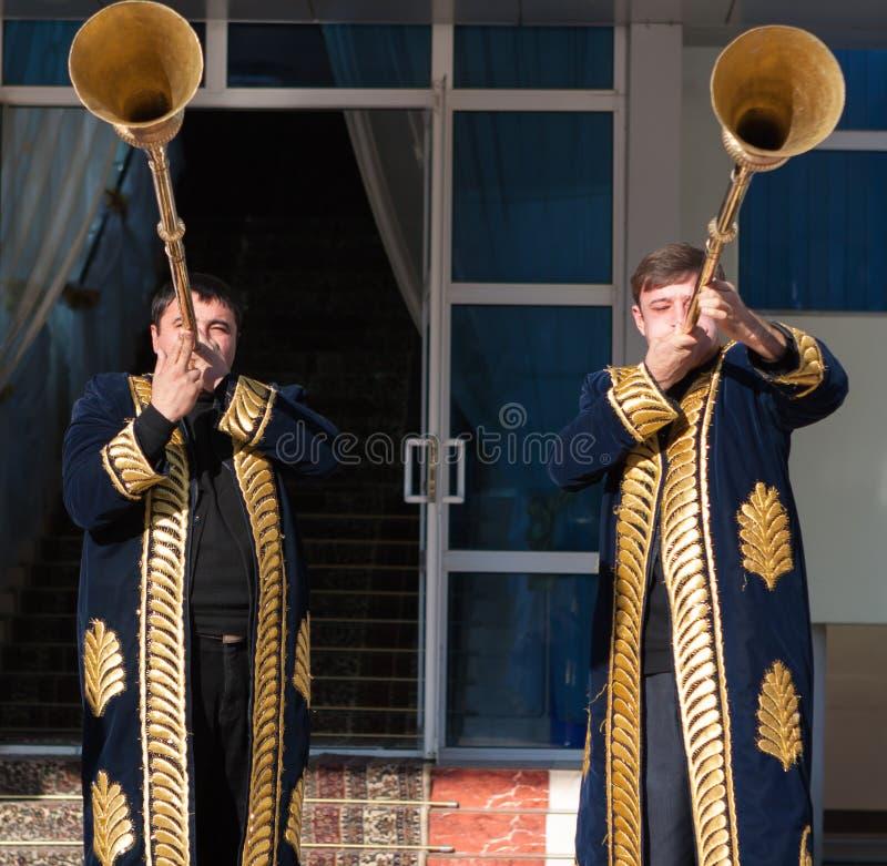 TASHKENT UZBEKISTÁN - 9 de diciembre de 2011: Hombres del músico en los kaftans tradicionales que juegan el karnay imagen de archivo