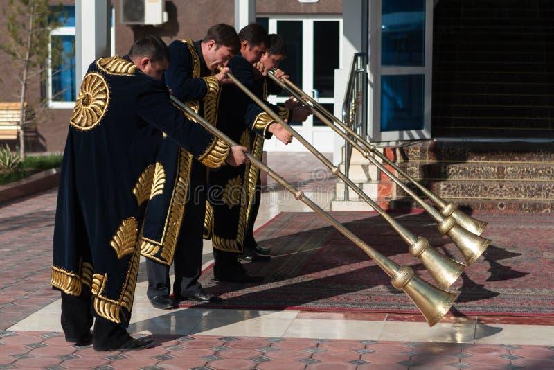 TASHKENT UZBEKISTAN, Grudzień 9 2011 -: Muzyków mężczyzna w tradycyjnych kaftans bawić się karnay zdjęcia royalty free