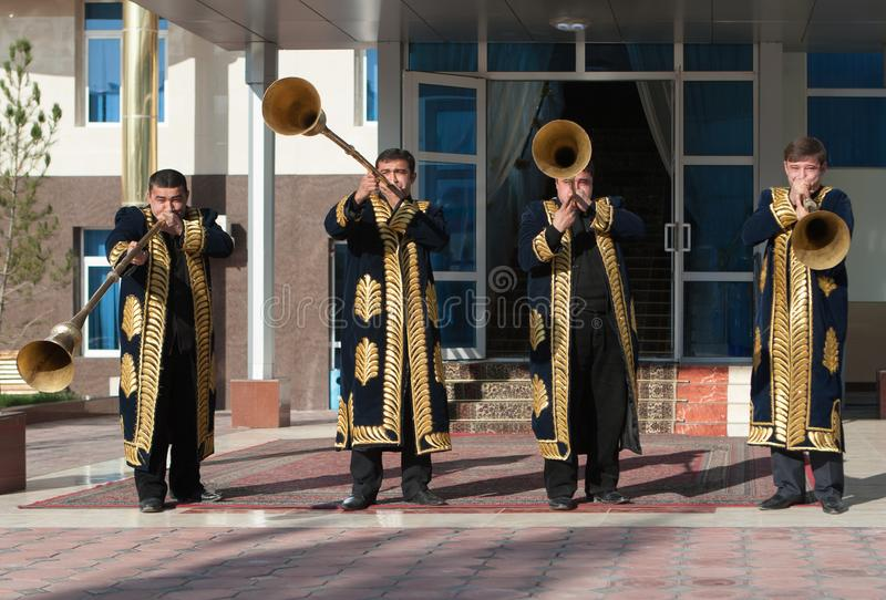 TASJKENT UZBEKISTAN - December 9 2011: Musikermän i traditionella kaftans som spelar det karnay royaltyfri foto