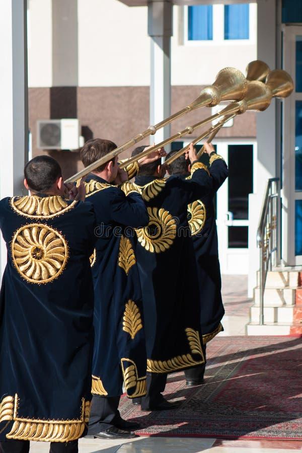 TASJKENT UZBEKISTAN - December 9 2011: Musikermän i traditionella kaftans som spelar det karnay arkivfoto