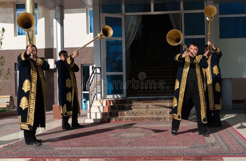 TASJKENT UZBEKISTAN - December 9 2011: Musikermän i traditionella kaftans som spelar det karnay royaltyfria bilder
